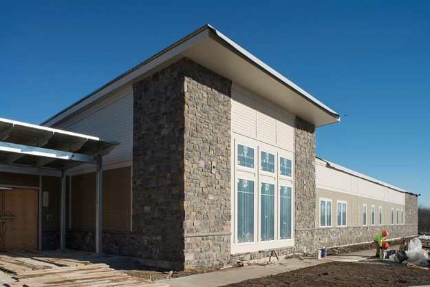 Exterior of AMC Latham Multi Specialty Building, beige siding with stone veneer.