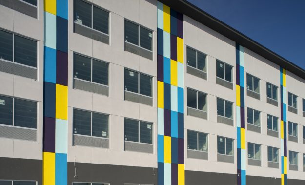 Exterior shot of Tru by Hilton hotel in Chicopee, MA. Predominantly grey with blue, purple, and yellow rectangular accents.